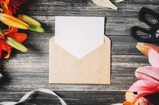 La tarjeta de la maqueta y el sobre blanco del arte con los lirios florece en un fondo de madera oscuro
