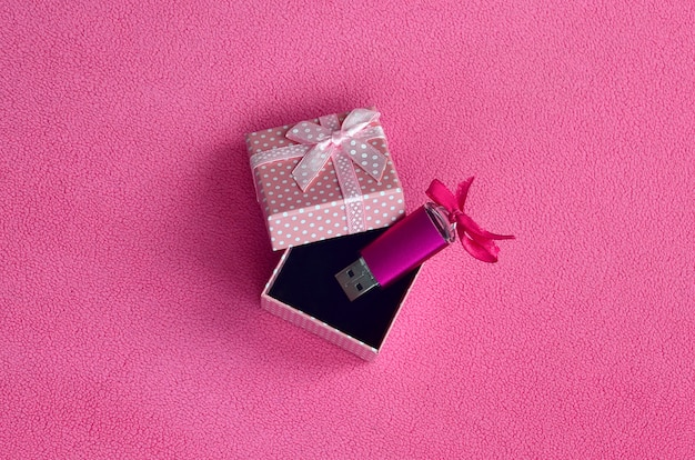 La tarjeta de memoria flash usb brillante de color rosa con un lazo rosado se encuentra en una pequeña caja de regalo de color rosa