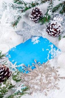Tarjeta de navidad con abeto decorado en la nieve.