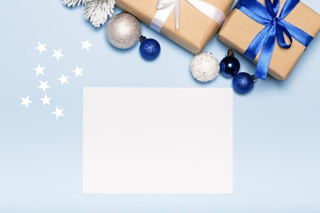 Tarjeta de navidad con caja de regalo de papel y bolas sobre fondo azul vacaciones