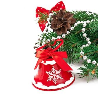 Tarjeta de navidad con una campana roja y ramas de abeto