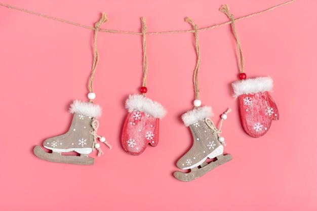 Tarjeta de navidad, decoración de año nuevo: mitones y patines de madera rojos se cuelgan en una cuerda