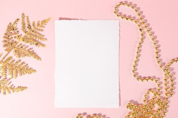 Tarjeta de navidad con decoración festiva dorada sobre un fondo rosa pastel.