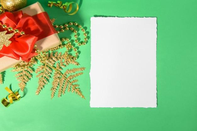 Tarjeta de navidad con decoración festiva de regalo dorado sobre fondo verde.