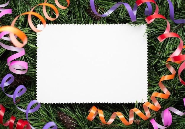 Tarjeta de navidad en el fondo de ramas de abeto y serpentinas festivas. nota blanca vacía
