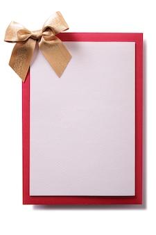 Tarjeta de navidad con lazo dorado y sobre rojo