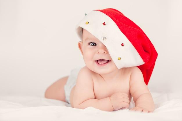 Tarjeta de navidad con una linda niña con un sombrero rojo de santa en un fondo de briht aireado beige con copia