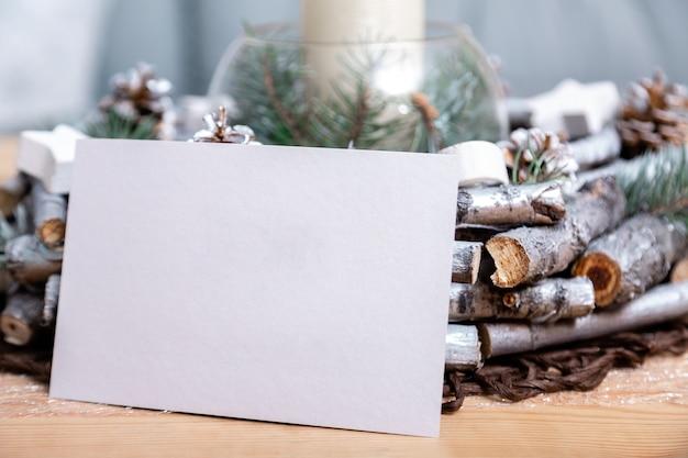 Tarjeta de navidad en la mesa cerca de la decoración navideña