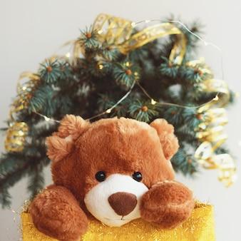 Tarjeta de navidad con oso de peluche en bolsa de regalo.