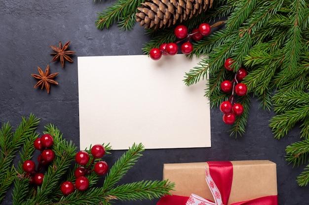 Tarjeta de navidad con papel, caja de regalo y rama de abeto sobre fondo negro