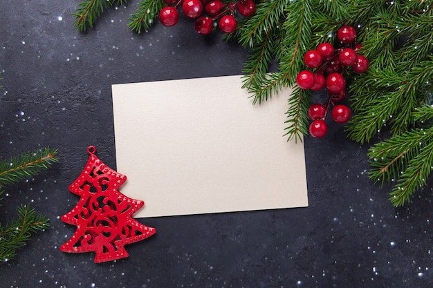 Tarjeta de navidad con papel y rama de abeto sobre fondo negro