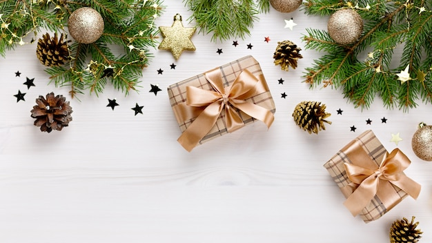 Tarjeta de navidad con ramas de abeto, cajas de regalo, decoración dorada y adornos de madera, confeti con nieve. navidad plana lay