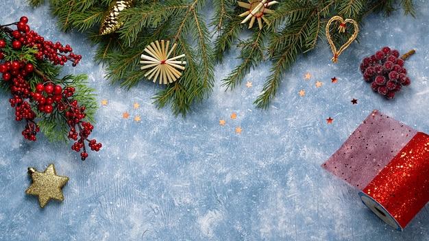 Tarjeta de navidad con ramas de abeto, cintas rojas y decoraciones, adornos de madera, confeti. navidad plana lay