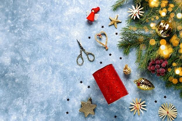 Tarjeta de navidad con ramas de abeto, cintas rojas y decoraciones, adornos de madera, confeti con nieve. navidad plana lay