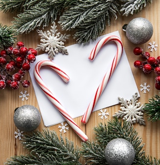 Tarjeta navideña de madera con decoración navideña, bastones de caramelo navideño, bolas navideñas y rama de abeto