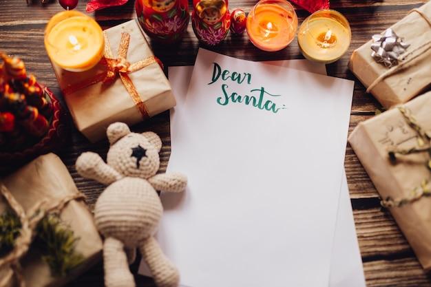 Tarjeta navideña con papel artesanal, caja de regalo, juguetes navideños hechos a mano y velas.