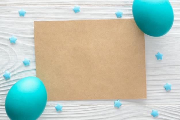 Tarjeta de papel con brillantes huevos de pascua en la mesa de madera.