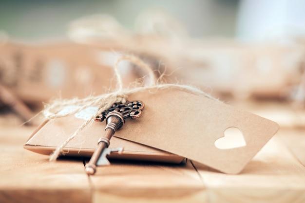 Tarjeta de papel con llave junto sobre un fondo de madera