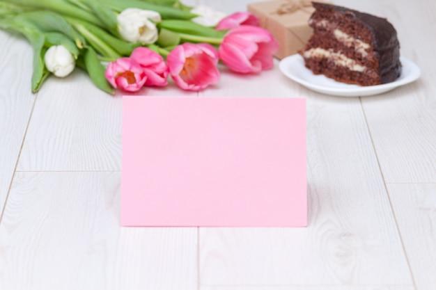 Tarjeta de papel, ramo de tulipanes rosados, pastel de chocolate. caja de regalo copia espacio