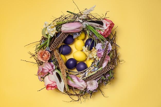 Tarjeta de pascua huevos de pascua pintados en nido en amarillo