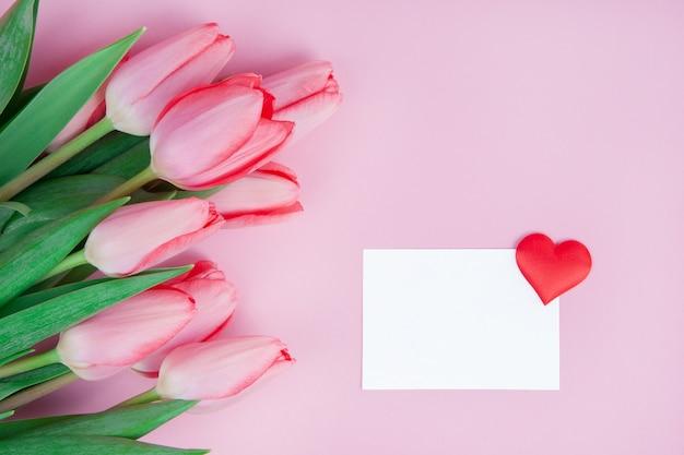 Tarjeta postal delicada flores tulipanes con una nota sobre un fondo rosa simulacro