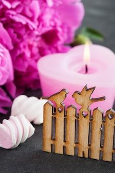 Tarjeta postal con puerta de madera y pájaros, flores de peonía, vela