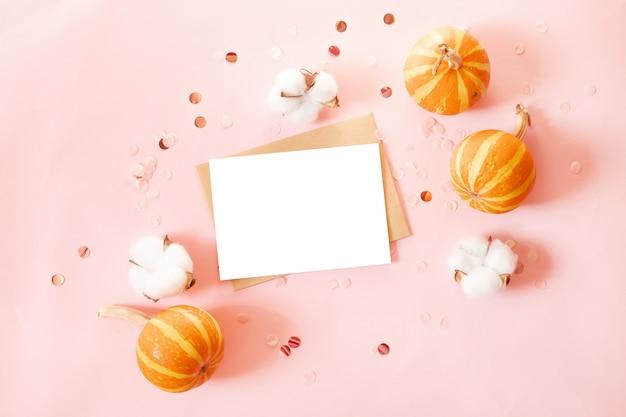 Tarjeta postal con sobre de papel artesanal y calabazas pequeñas, decoración brillante y flores de algodón