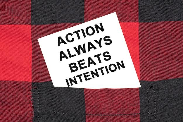 Tarjeta de presentación blanca con el texto action always beats intention se encuentra en la manga de una camisa a cuadros