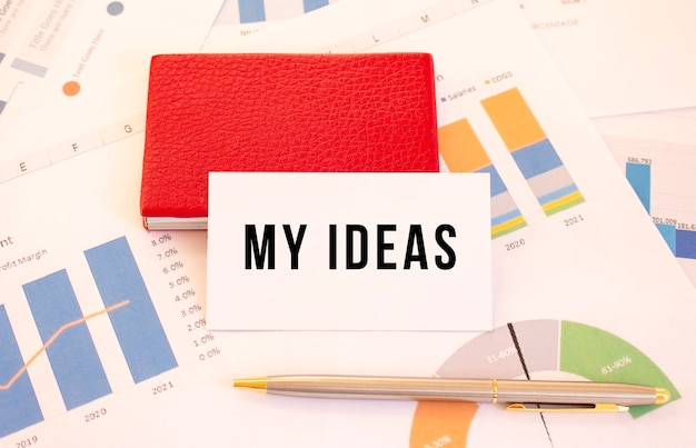 Una tarjeta de presentación blanca con el texto mis ideas se encuentra junto al portatarjetas de presentación rojo