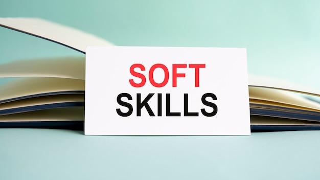 Una tarjeta de presentación blanca con texto de soft skills se encuentra en un escritorio con el telón de fondo de un diario abierto. desenfocado
