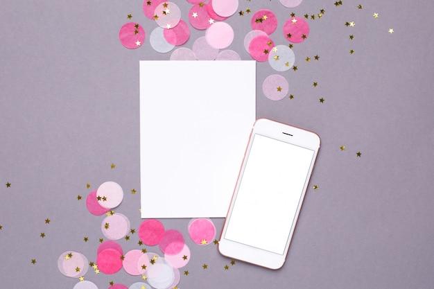 Tarjeta de presentación, maqueta de teléfono móvil y confeti rosa con estrellas doradas en gris