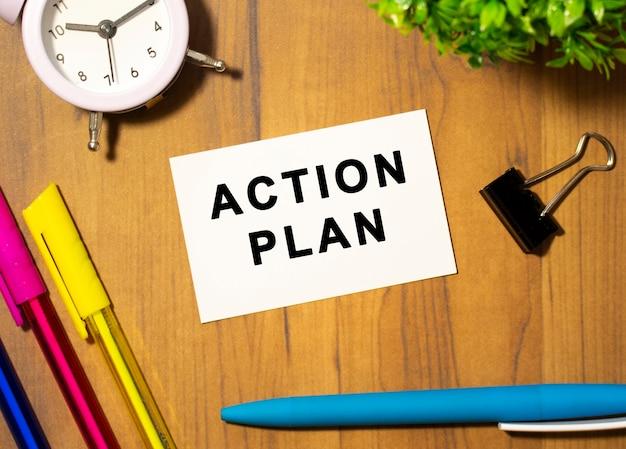 Una tarjeta de presentación con el texto plan de acción se encuentra en una mesa de oficina de madera entre suministros de oficina. concepto de negocio.