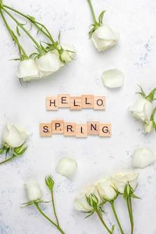 Tarjeta de primavera con rosas blancas y flores, vista superior