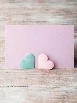 Tarjeta púrpura de los corazones en colores pastel rosada y verde