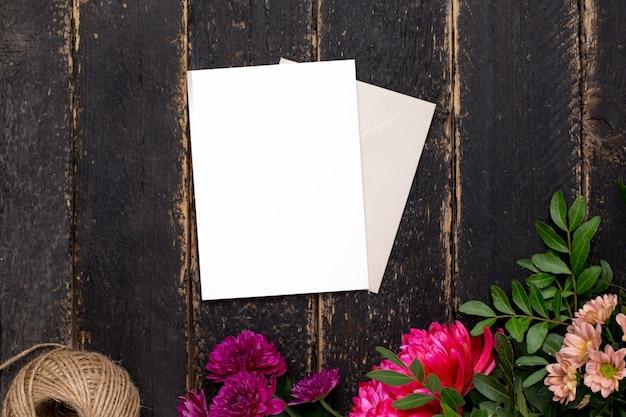 Tarjeta de regalo blanca con hermosas flores en una mesa oscura vintage