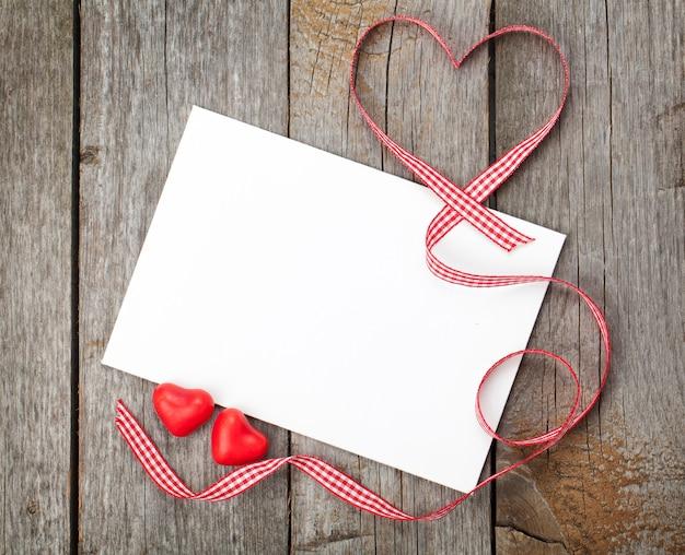 Tarjeta de regalo en blanco del día de san valentín y corazones de caramelo rojo sobre fondo de madera