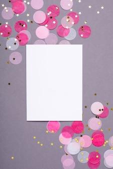 Tarjeta de regalo y confeti rosa con estrellas doradas en gris