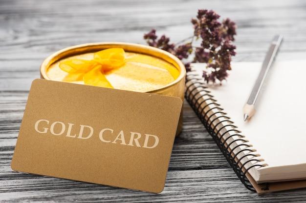 Tarjeta de regalo dorada, cuaderno, vela y caja