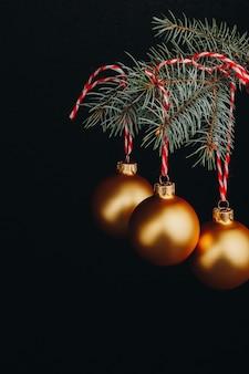 Tarjeta de regalo de navidad y año nuevo. ramas de abeto y decoración con bolas de oro con hilo rojo sobre un fondo negro aislado