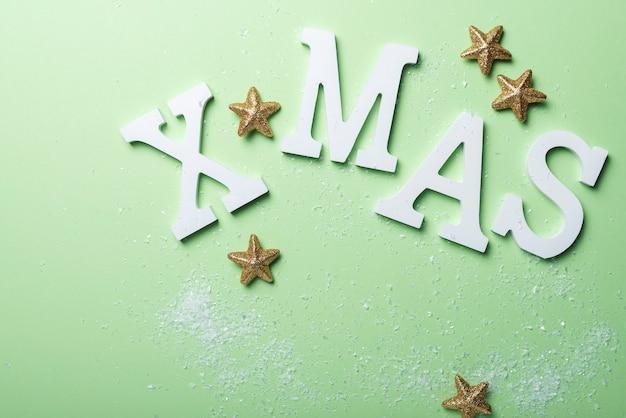 Tarjeta de regalo de navidad con letras blancas sobre fondo verde. concepto de vacaciones, vista de arriba hacia abajo