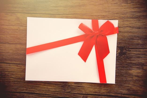 Tarjeta de regalo sobre fondo de madera tarjeta de regalo rosa blanca decorada con lazo de cinta roja para feliz navidad, feliz año nuevo o día de san valentín