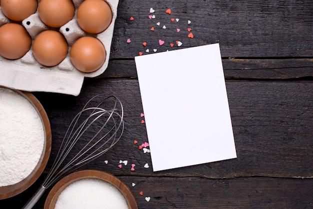 Tarjeta de regalo, utensilios de cocina y corazones en madera