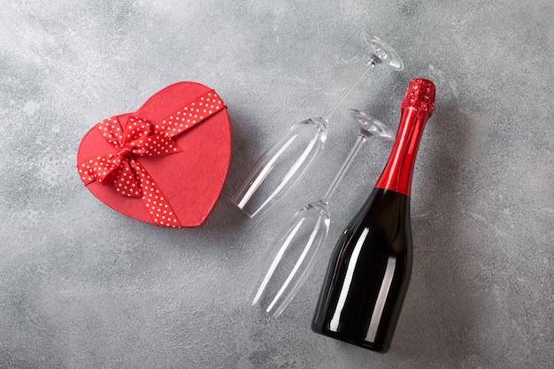 Tarjeta de san valentín con una botella de champán, vasos con una caja de bombones en forma de corazón.