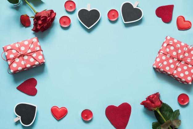Tarjeta de san valentín composición con regalos, corazones rojos sobre fondo azul.