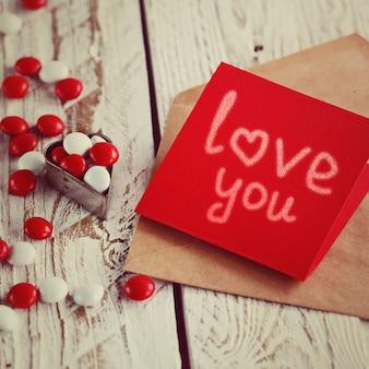 Tarjeta de san valentín con corazones pequeños y caramelo blanco rojo. imagen tonificante.