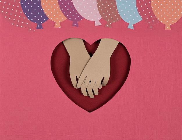 Tarjeta de san valentín. papel creativo cortado con globos de papel brillante y mirada de las manos de los amantes.