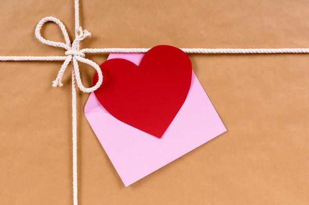 Tarjeta de san valentín en un paquete de papel marrón o un regalo atado con una cuerda.