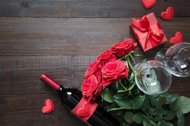 Tarjeta de san valentín con románticas rosas rojas, botella de vino, corazón y caja de regalo roja en mesa de madera. vista superior con espacio.