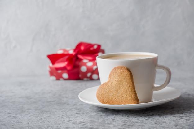 Tarjeta de san valentín. taza blanca de café con leche con leche, galletas de corazón y regalo. de cerca.