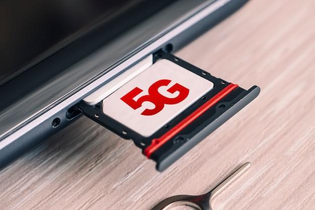Tarjeta sim etiquetada 5g. reemplazo de una tarjeta sim en un teléfono móvil con internet de alta velocidad.